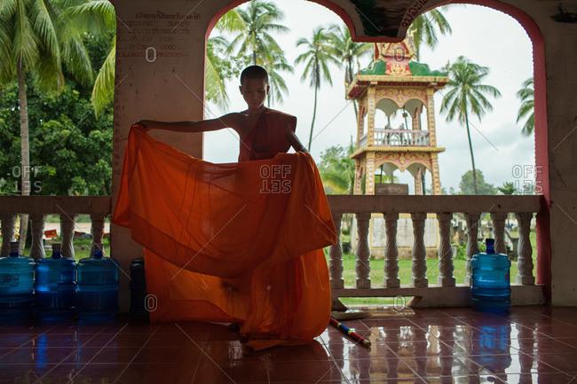 Wat Khon Tai Pagoda, Don Khon Island, Cambodia - August 3, 2013: A Buddhist monk preparing his robe
