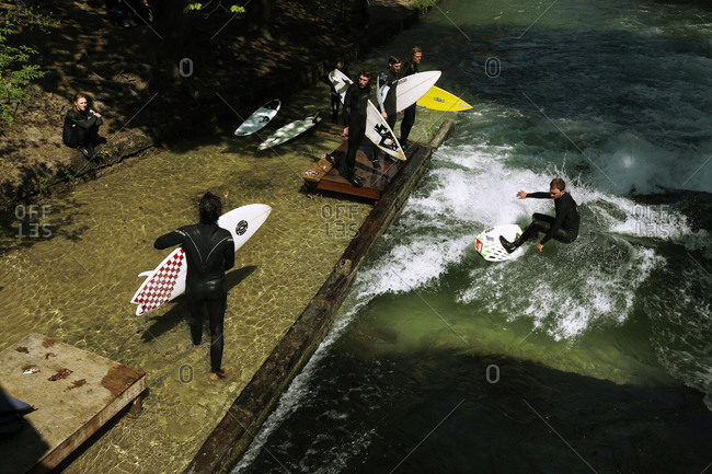 Munich, Germany - April 19, 2011: Young men river surfing on Eisbach river, Munich