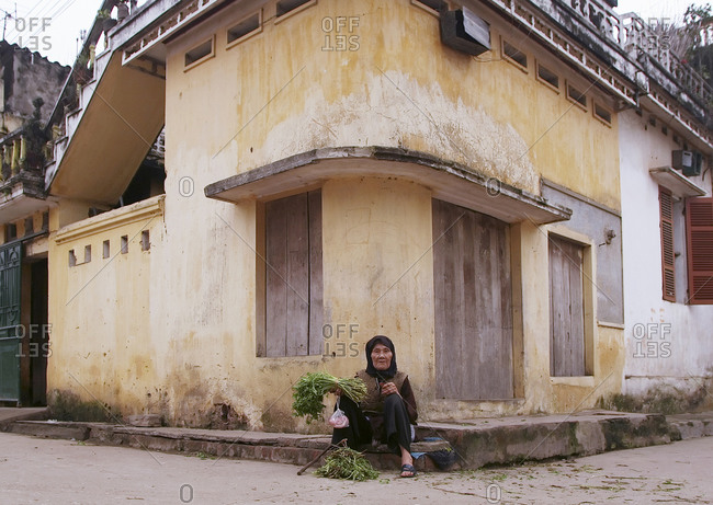 Lam Son Village, Vietnam - April 2, 2005: Low angle view of an elderly woman sitting on a street corner