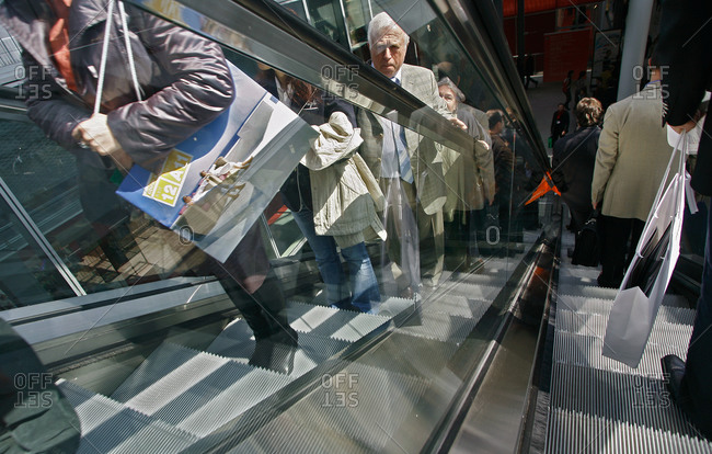 Milan, Italy - April 7, 2006: People standing on an escalator in Milan, Italy