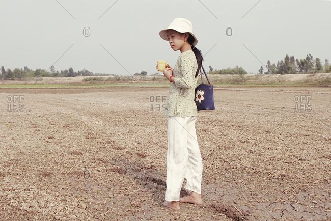 Vietnam - March 22, 2005: Young girl standing in the field in Vietnam