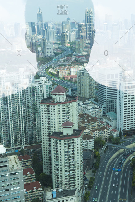 A man's reflection in a widow reveals a massive city