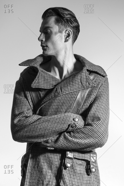 A man in a checkered coat turns to the side