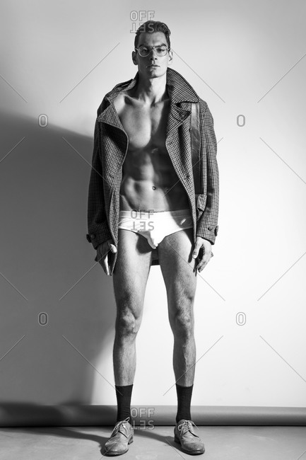A man wears only a coat and underwear