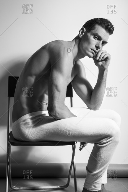 A man in long johns sits on a chair