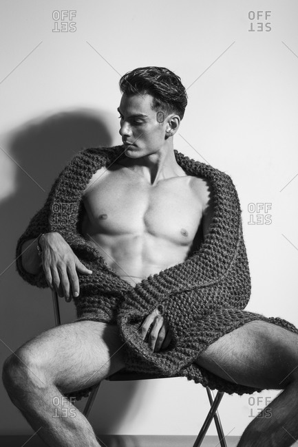 A man sits in a chair wearing only a sweater