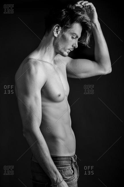 A shirtless man touches his hair