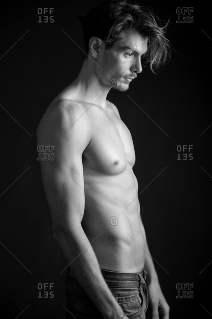 A shirtless man looks into the distance