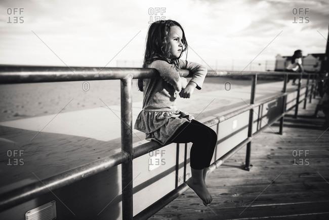 Girl sitting on boardwalk railing