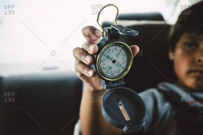 Young boy holding up compass in car