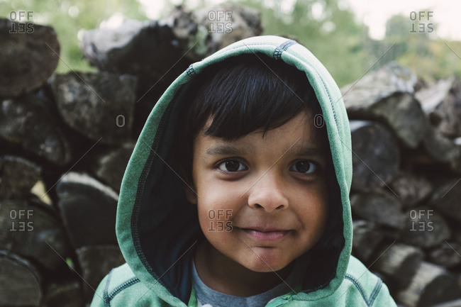 Young boy smiling by woodpile