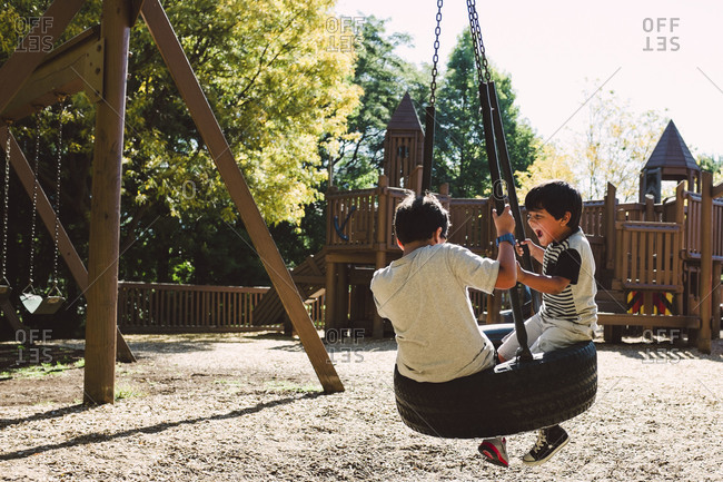 Two boys in playground on tire swing