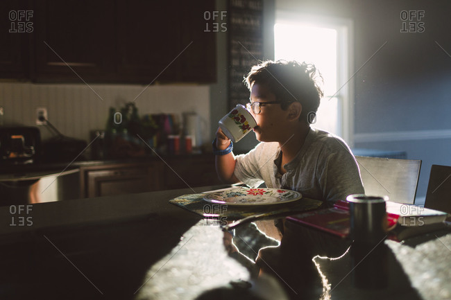 Boy sipping from cup at breakfast