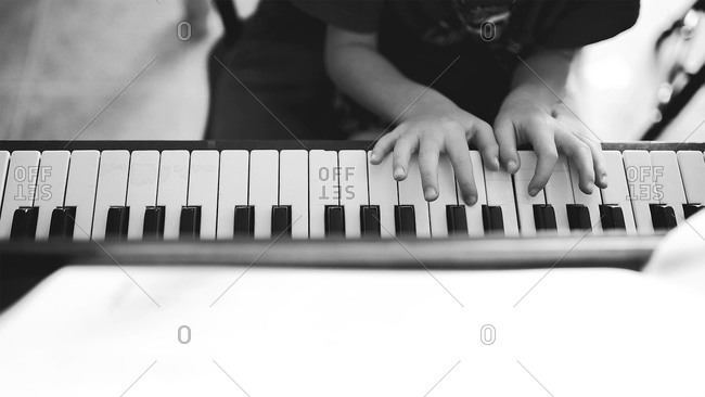 A boy playing a piano keyboard