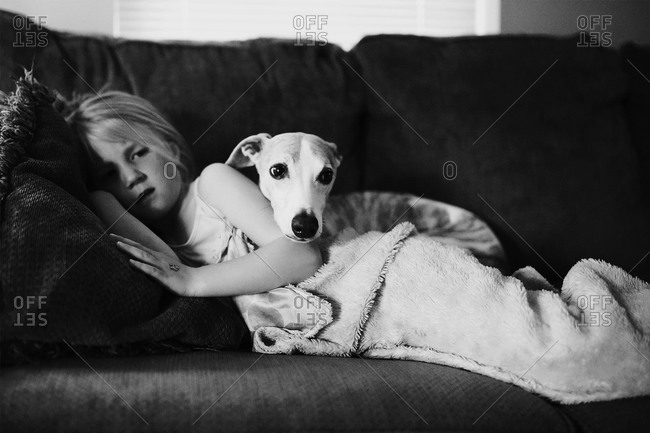 A girl and dog snuggling on couch