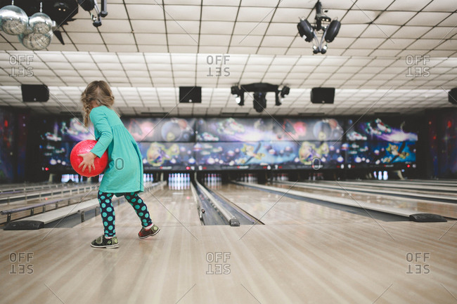 A girl in bowling alley holding ball