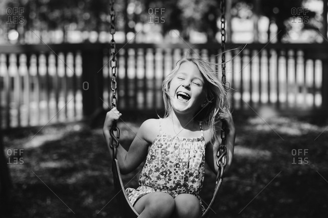 Girl laughing on a swing