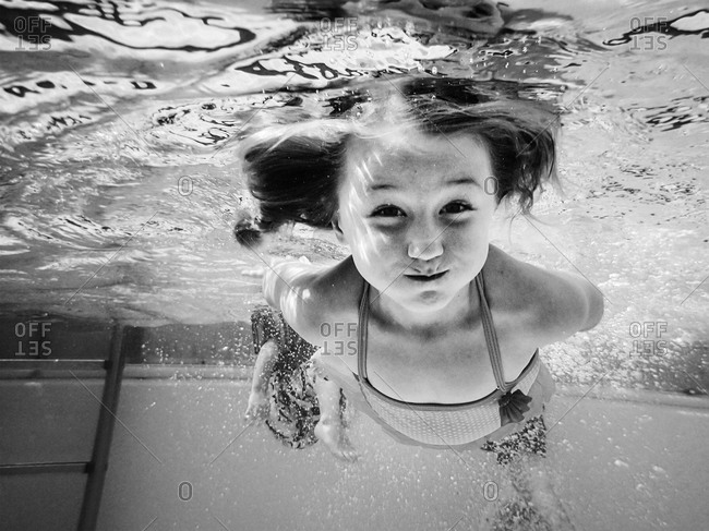 Little girl floating underwater in pool