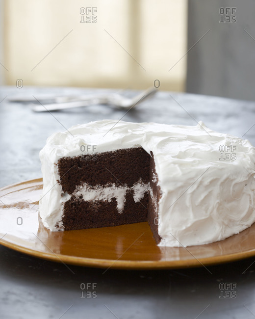 Vanilla frosting covers chocolate cake