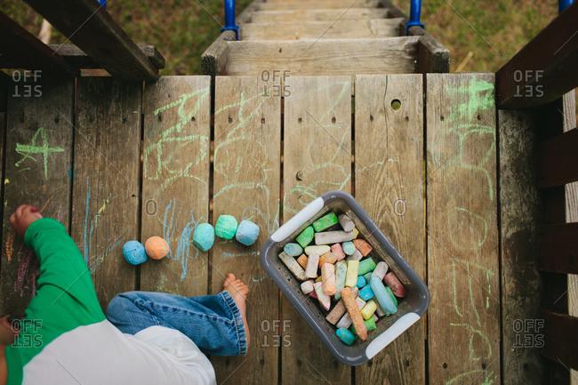 A boy colors a deck with chalk