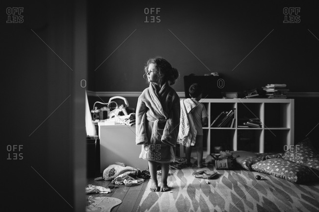 Two children stand in a messy room