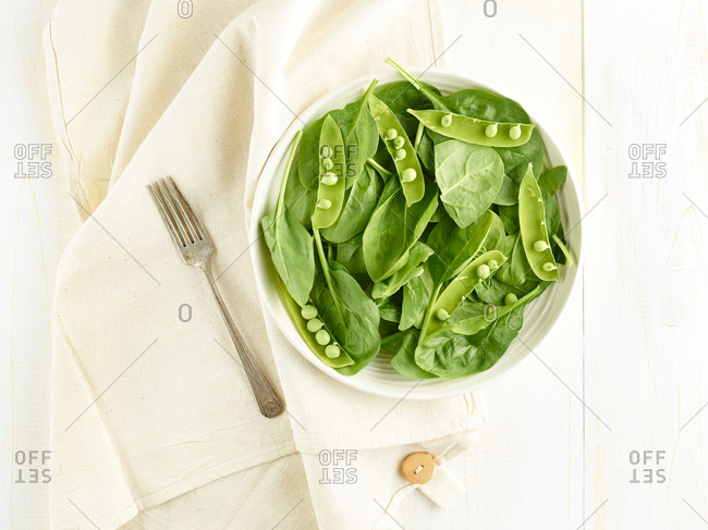 Spinach leaves and pea shells sit in a bowl