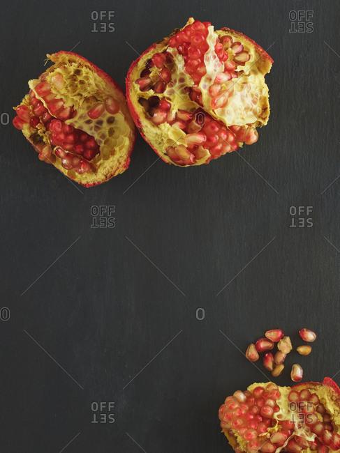 Halved pomegranates lay on a dark background