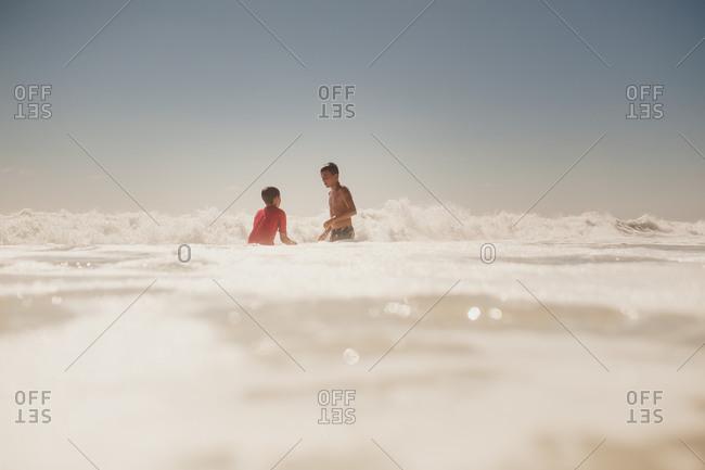 Two boys standing in ocean water