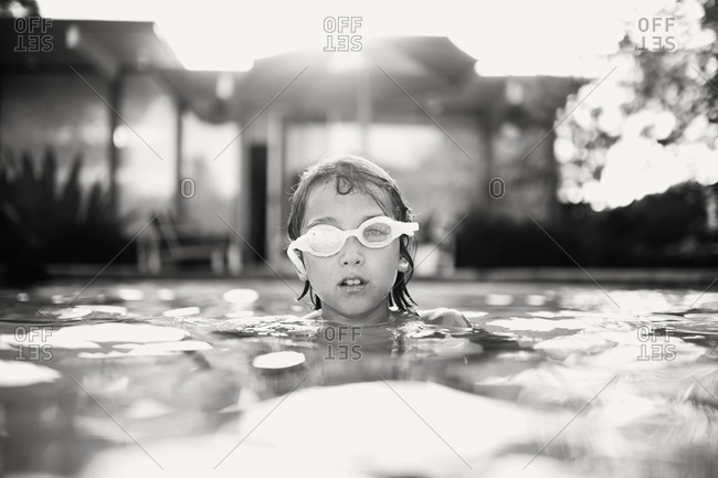 A girl neck deep in a pool