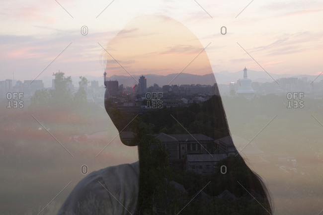 A woman and a cityscape reflect in glass