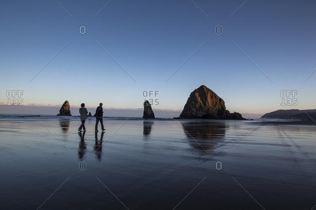 A family walks across a beach