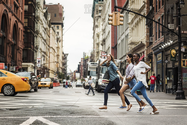 Three young women crossing the street together