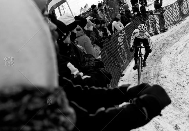 Louisville, KY - February 2, 2013: Cyclocross racer along curve near crowd