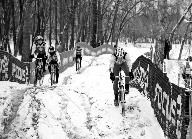Louisville, KY - February 2, 2013: racers traversing snowy rises on Cyclocross course
