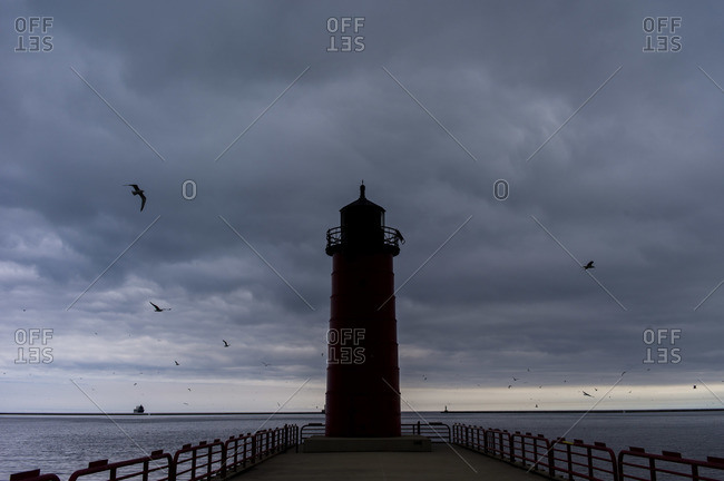 Lake lighthouse with ship off in distance
