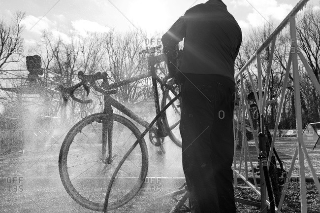 Louisville, KY - February 1, 2013: Cyclocross racer hoses his bike down