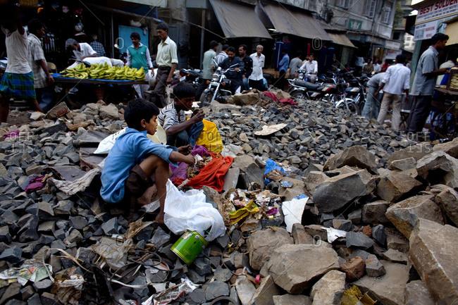 Mumbai, India - November 19, 2006: Two boys in Mumbai market scavenging through garbage