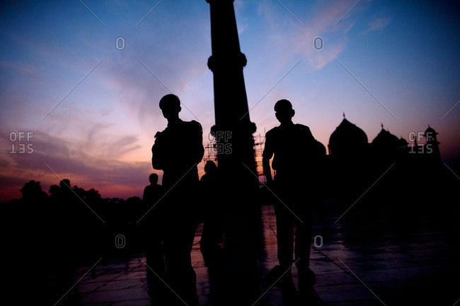 Taj Mahal and tourists silhouetted by sunset