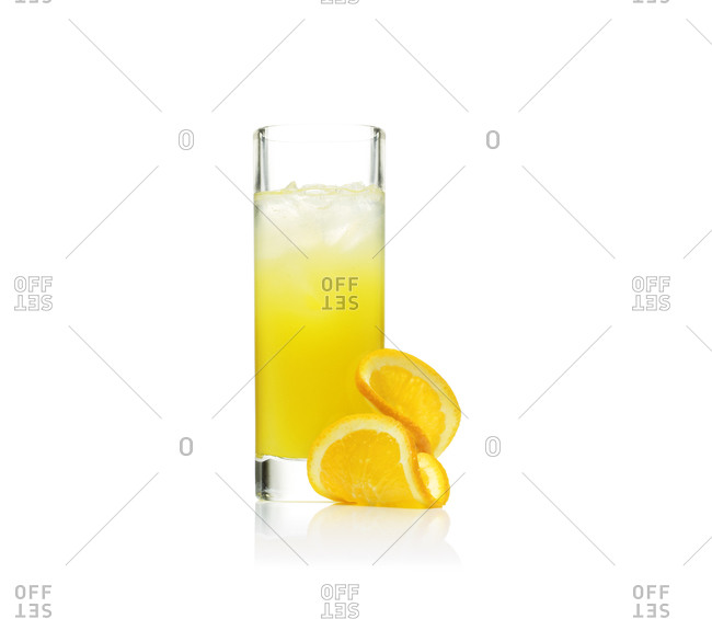 Orange slices sit next to a screwdriver cocktail in Collins glass
