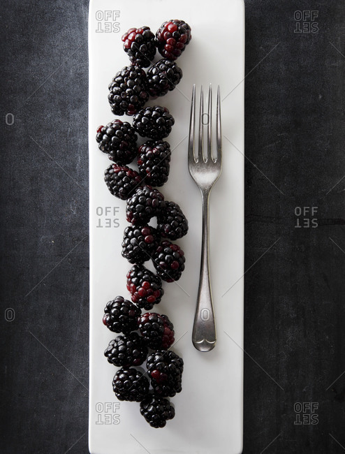 Blackberries line up next to a fork