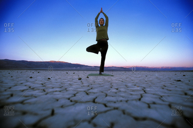 Woman doing yoga tree pose at sunrise in Death Valley, California