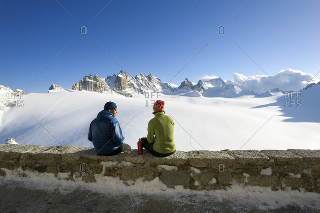 Friends relaxing on hut deck after ski touring in the Swiss Alps