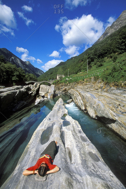 A woman reading and napping along the river in the Valle Verzasca, Lavartezzo, Ticino, Switzerland