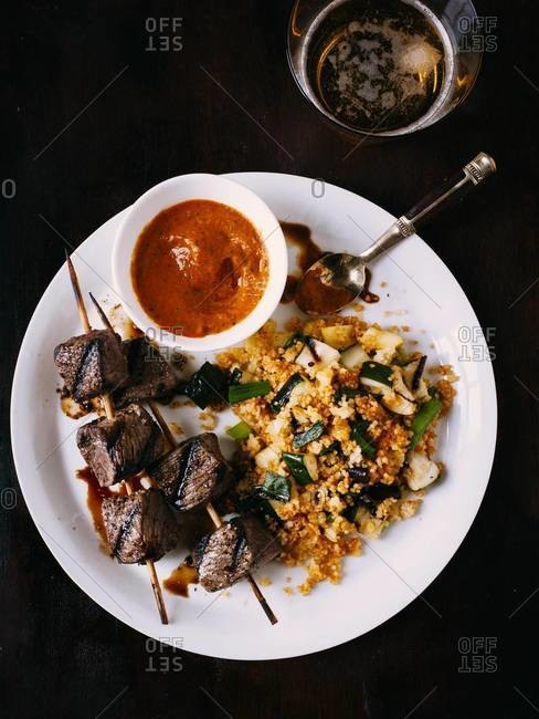 Grilled beef skewers with spicy dipping sauce, vegetable couscous seasoned with spices