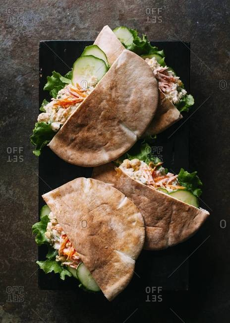 Top view of pitas seasoned white beans with lettuce, carrots and cucumber