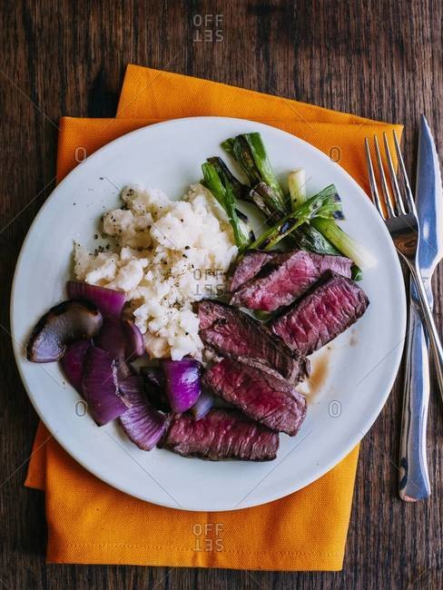 Beefsteak served with mashed potatoes and roasted scallion