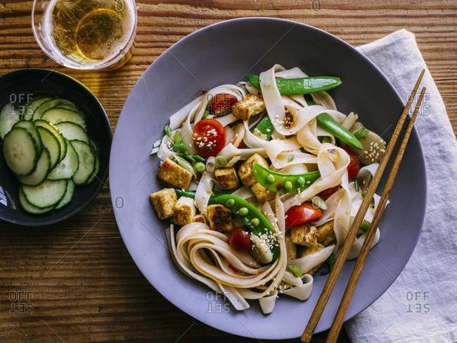 Rice noodle with sugar snap peas served on a table