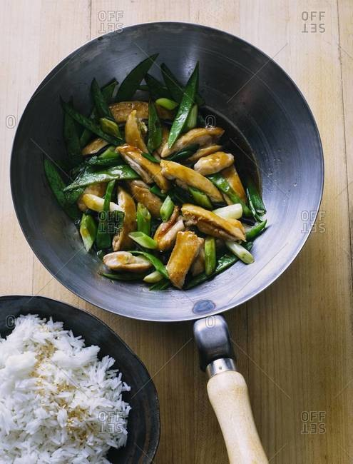 Chicken with snow peas and green onions stir fry in wok