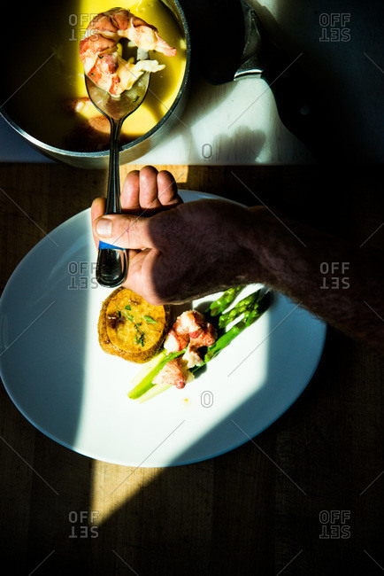 Chef plating butter-poached lobster with asparagus and new potatoes
