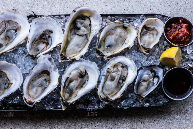 Top view of oysters on the half shell with dips and lemon